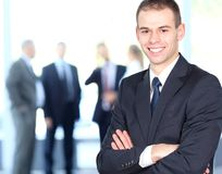 Handsome happy business man with colleagues. At the back Royalty Free Stock Images