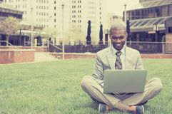 Handsome happy businessman working with laptop outdoors Stock Photos