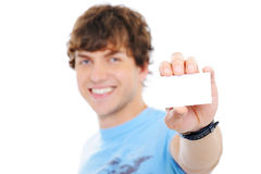 Handsome happy guy showing the blank card. On foreground - soft focus Royalty Free Stock Photography