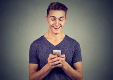 Handsome happy man using a smartphone stock photography