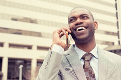 Handsome happy laughing young businessman talking on mobile phone Stock Images