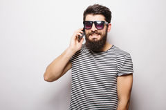 Handsome happy man with beard in sunglasses talking on the phone Stock Image