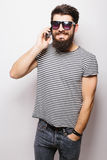 Handsome happy man with beard in sunglasses talking on the phone Royalty Free Stock Photos