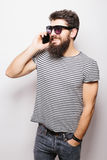 Handsome happy man with beard in sunglasses talking on the phone Stock Images
