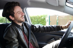 Handsome happy man driving car laughing Royalty Free Stock Image