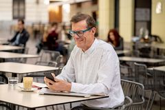 Smiling attractive stylish mature man using smart phone checking online sitting outside coffee shop stock photos