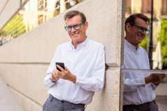 Handsome happy man in his 60s sending and receiving text messages on his mobile phone in old man using social network modern royalty free stock image