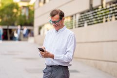 Handsome happy man in his 60s sending and receiving text messages on his mobile phone in old man using social network modern stock photography