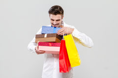 Handsome happy man holding colorful gifts Stock Photography
