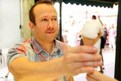Handsome happy man sells ice cream in shop. Kind female seller in candy store gives ice cream to boy. royalty free stock photography