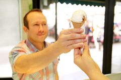 Handsome happy man sells ice cream in shop. Kind female seller in candy store gives ice cream to boy. Handsome happy men sells ice cream in shop. Kind female Stock Photos