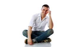 Handsome happy man sitting at the floor royalty free stock photo