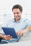 Handsome happy man sitting on the sofa using his tablet pc Royalty Free Stock Photo