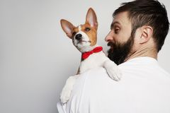 Handsome happy man snuggling and hugging his basenji puppy dog, close friendship against a white background. Handsome happy man snuggling and hugging his royalty free stock photo