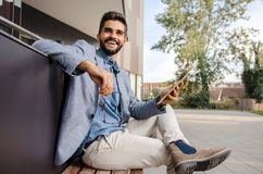Handsome happy man in suit sitting on bench royalty free stock photos