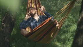 Handsome happy man talking by cellphone lying in hammock. Male speaking on mobile phone and swinging in hammock. Relax in hammock.