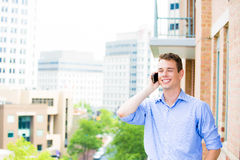 Handsome, happy man talking on his cell phone while on his outside balcony Stock Images