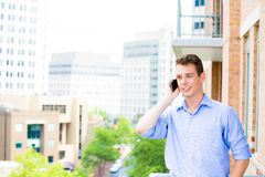 Handsome, happy man talking on his cell phone while on his outside balcony Royalty Free Stock Image