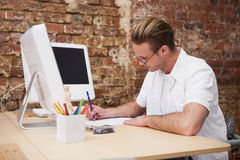 Handsome happy man using computer taking notes Royalty Free Stock Photography