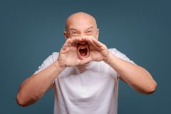 Handsome happy man wearing white T-shirt, guy speaking loudly, isolated on blue background stock photo