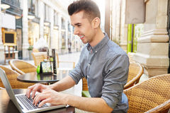 Handsome happy man working at cafe typing on laptop Stock Photo