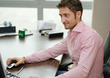 Handsome, happy office worker smiling while using computer Royalty Free Stock Photography