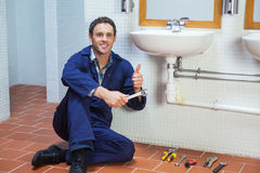 Handsome happy plumber sitting next to sink showing thumb up Royalty Free Stock Image