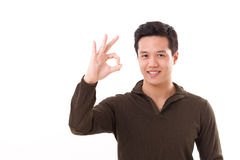 Handsome, happy, smiling man giving ok hand sign Stock Photo