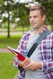 Handsome happy student carrying folder Stock Photos