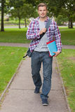 Handsome happy student carrying notebook and folder Royalty Free Stock Images