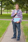 Handsome happy student holding notebook and folder Stock Image