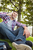 Handsome happy student sitting on grass phoning Stock Images