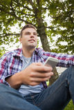 Handsome happy student sitting on grass texting Stock Photo