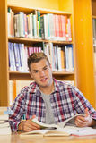 Handsome happy student studying his books stock image