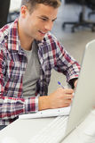 Handsome happy student using computer taking notes Stock Photography
