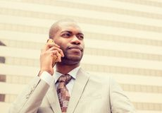 Handsome happy young businessman talking on mobile phone Stock Image