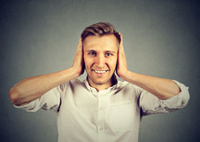 Handsome happy young man covering his ears. On gray wall background. Hear no evil concept Royalty Free Stock Image