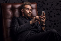 Handsome happy young man in dark suit relaxing on luxury sofa. Stock Images