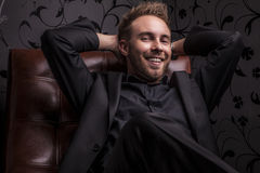 Handsome happy young man in dark suit relaxing on luxury sofa. Stock Photography