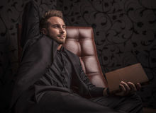 Handsome happy young man in dark suit relaxing on luxury sofa. Royalty Free Stock Photos