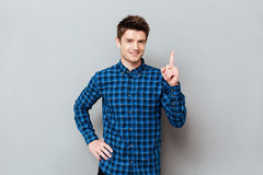 Handsome happy young man standing over grey wall and pointing. Image of handsome happy young man standing over grey wall and pointing. Looking at camera royalty free stock images