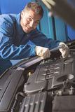 Handsome hardworking mechanic repairing a car Royalty Free Stock Images