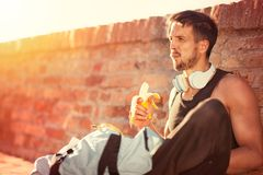 Handsome healthy male runner taking break after fitness workout. And exercising, break for healthy snack Stock Images