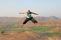 Handsome high jump man. A bald man wearing sunglasses in Hampi, jumps high on Anjaneya Hill, Hanuman Temple. Rice fields or. Terraces, large stones in Hampi stock photography