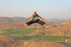 Handsome high jump man. A bald man wearing sunglasses in Hampi, jumps high on Anjaneya Hill, Hanuman Temple. Rice fields or. Terraces, large stones in Hampi stock photos
