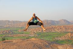 Handsome high jump man. A bald man wearing sunglasses in Hampi, jumps high on Anjaneya Hill, Hanuman Temple. Rice fields or. Terraces, large stones in Hampi royalty free stock image