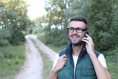 Handsome hiker with glasses talking on mobile phone and looking at away with gorgeous green view of nature stock photo