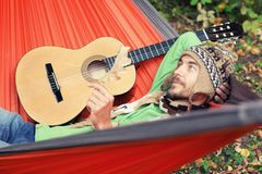 Handsome hiker with guitar relax in a hammock after trip in the Royalty Free Stock Image