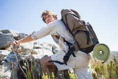 Handsome hiker hiking through rough terrain Stock Images