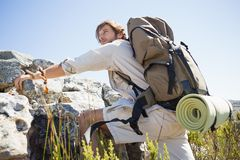 Handsome hiker hiking through rough terrain Royalty Free Stock Image